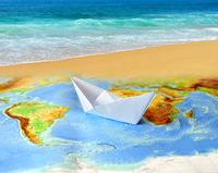 Paper boat on a background map of the world
