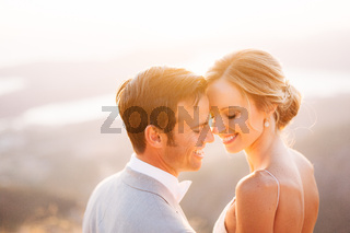 The bride and groom sitting on the top of Mount Lovcen overlooking the Bay of Kotor, smiling and hugging tenderly, close-up