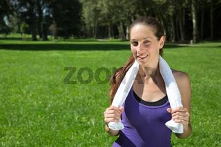 Sportliche Frau mit Handtuch macht eine Pause beim Laufen