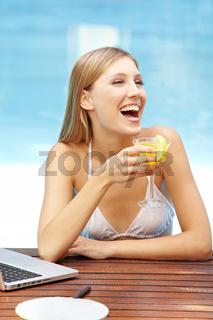 Lachende Frau mit Cocktail am Pool