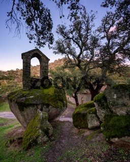 Ancient ruin stone structure building covered with moss near Sao Pedro chapel with trees and boulder landscape in Monsanto, Portugal