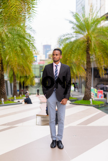 Full length portrait of handsome young African businessman thinking outdoors in city