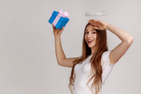Portrait of young friendly woman holding blue wrapped gift box and looking far, smiling at camera