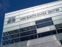 Teilansicht der Fassade des Ars Electronica Center mit Logo und Unschrift - Linz