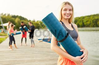 Junge Frau mit Yogamatte nach einem Fitness Kurs
