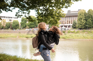 The daughter kisses her mom while walking in the waterfront