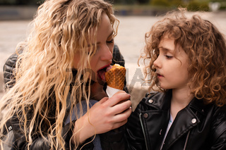 The mom gives her daughter a try ice cream