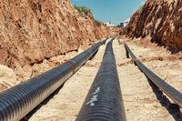 Metal technological pipelines in a trench in the middle of the steppe