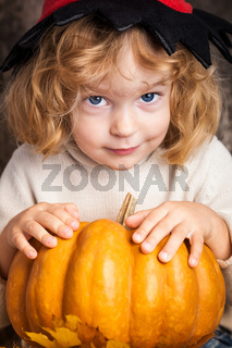 Beautiful child holding a pumpkin