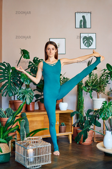 Young sporty woman practicing stretching yoga exercise at home doing Extended Hand to Big Toe