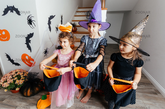 Girls receiving bunch of candies during halloween trick or treating