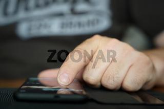 Die Finger einer Person bedienen ein auf dem Tisch liegendes Smartphone
