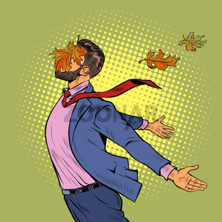 a joyful man in autumn maple leaves stands in the wind, opened his hands to the elements
