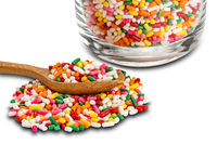 Rainbow sprinkles in transparent glass and in wooden spoon isolated on white background.