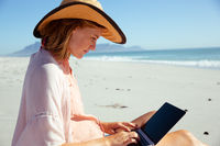 Woman using laptop at the beach