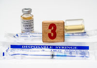 Concept for Covid-19 booster dose or shot using wooden three block with wrapped disposable syringes