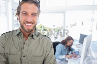 Cheerful man in creative office with arms folded