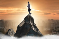 Businessman at the top of mountain in career concept