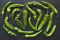 Top view of whole green peppers on dark background