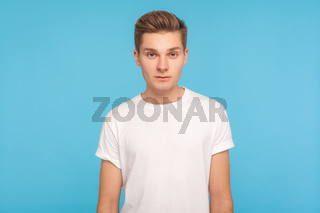 Portrait of emotional young man on blue background.