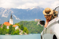 Happy young woman on vacation leaning out of car window on shore of Bled lake, country of Slovenia. Travel, holiday, tourism, explore, rent a car concept.