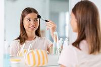 teenage girl applying powder to face at bathroom