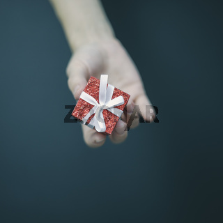 A tiny shiny red box with a white bow lies in women's fingers