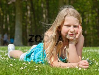 Teenager girl lying on grass