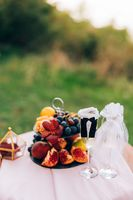 A painted table with a bookcase with fruits and glasses for champagne in the suits of the bride and groom.