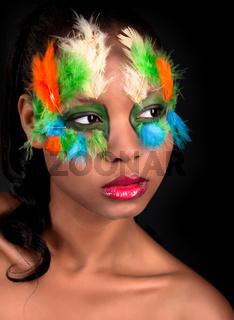 Gesicht einer schoenen jungen farbigen Frau mit bunten  Vogelfedern besetzt
