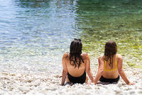 Two beautiful young woman's friends sitting on the beach, talking and having rest