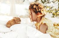 Little pretty girl in summer dress sitting outside with little rabbit