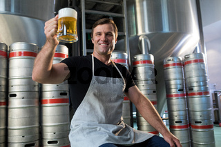 Portrait of smiling worker holding beer glass