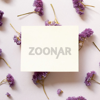 Empty memo note with dry statice flowers on purple background. Floral composition, flat lay, top view, copy space