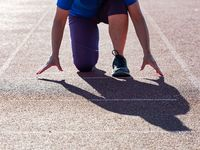Woman on athletics track exercises in position of start