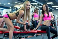 Handsome girls posing while exercising in gym