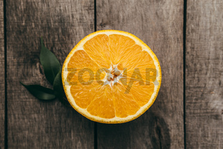 Sliced halves of orange fruit on gray wooden background. Pulp and green leaves