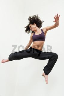 Junge Frau springt fröhlich in die Luft