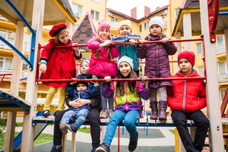 the smiling kids are standing together on the playground equipment