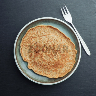 Delicious spelt pancake on a blue stoneware plate, too view