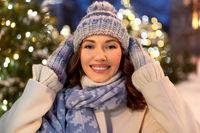 happy woman walking in christmas city in winter