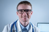 Happy confident male professional medic doctor close up portrait. Smiling doctor wear uniform looking at camera in office. Close-up of handsome German smile general practitioner wearing glasses
