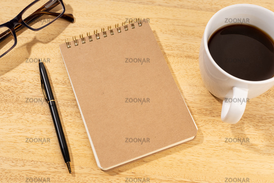 Blank Cardboard notepad on wooden desk with cup of coffee and eyeglasses. Template mock up
