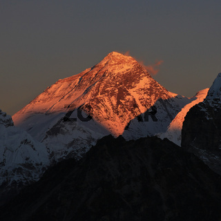 Illuminated peak of Mt Everest at sunset.