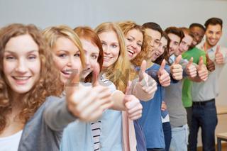 Lachende Schüler halten Daumen hoch