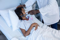 Midsection of male doctor putting oxygen mask ventilator on sick mixed race girl in hospital bed
