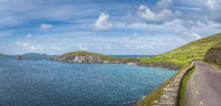 Panorama with narrow winding road on the edge of cliff, Coumeenoole Beach and islands in Dingle