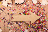 Arrow cut out of paper amid pencil shavings
