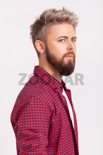 Side view portrait of handsome concentrated bearded young adult man in plaid t-shirt thoughtfully looking to side
