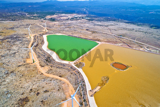 Wind power turbines under Velebit mountain view, Alkaline pool from abandoned factory